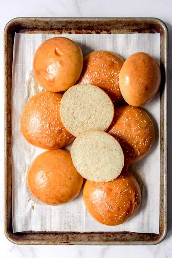 An image of homemade brioche sesame seed buns on a baking sheet.