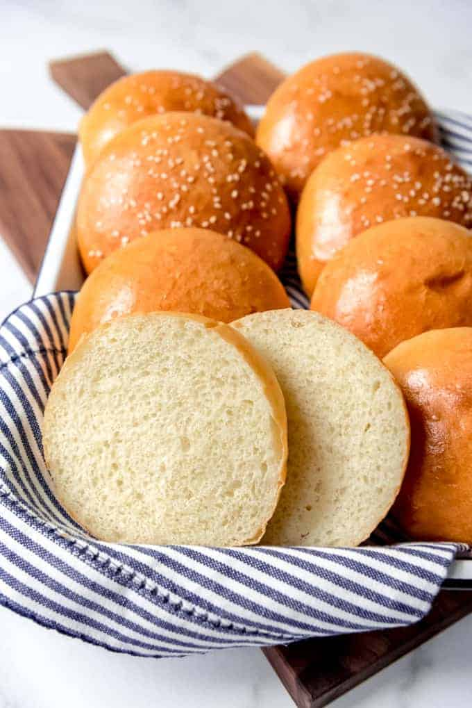 Sesame seed hamburger buns with one bun sliced open to show the soft insides.
