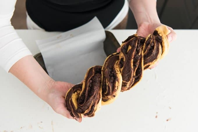 hands holding up a loaf of raw pumpkin babka bread about to be placed in a loaf pan