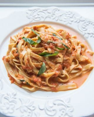 Creamy roasted pepper alfredo in a white plate garnished with chopped basil