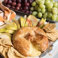 baked brie with puff pastry on a plate with grapes and apple slices