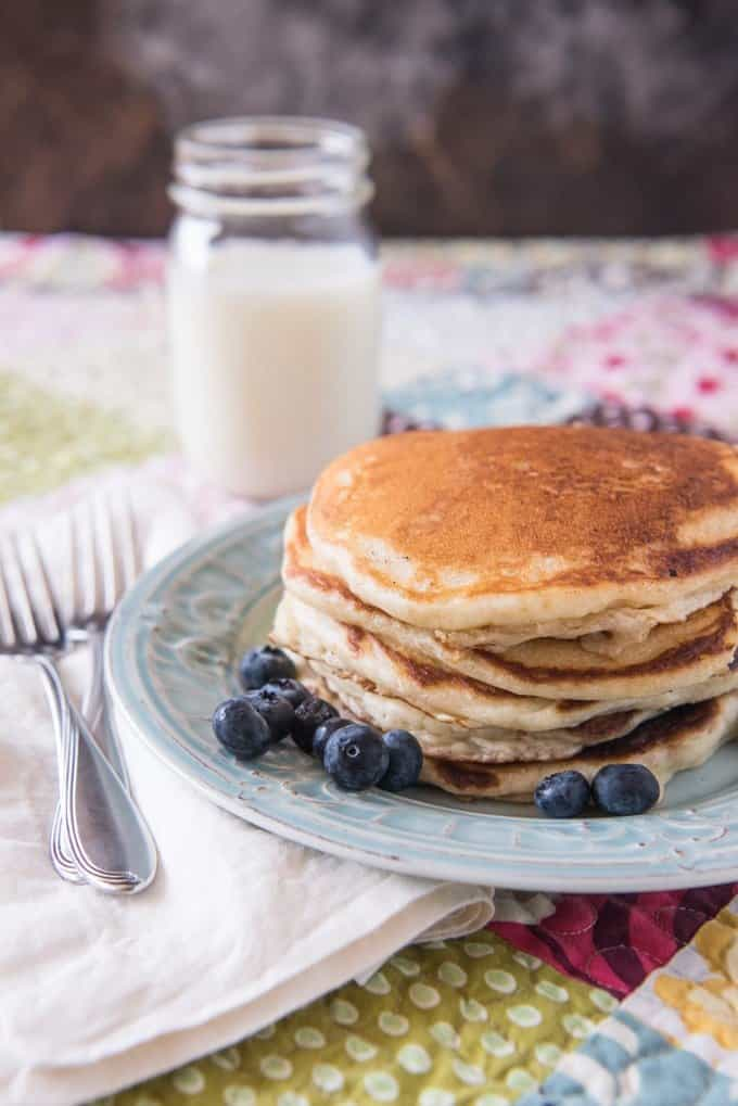 a stack of pancakes on a plate with blueberries