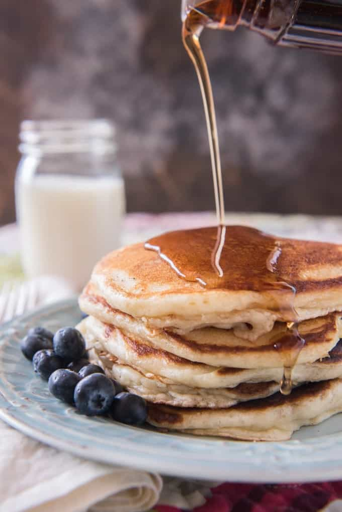 Pouring syrup on a stack ofgolden pancakes with fresh blueberries and a glass of milk to the side