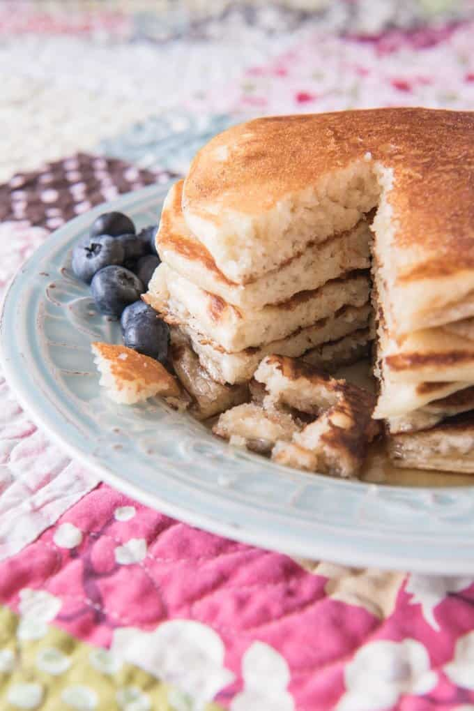 a stack of pancakes with fresh blueberries to the side and the pancakes are missing a bite