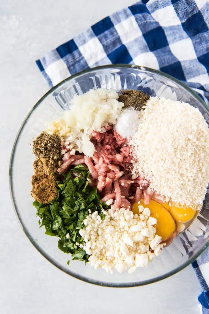 Ingredients needed to make lamb meatballs in a glass bowl