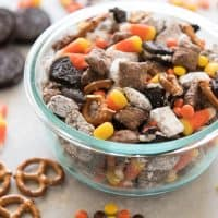 halloween chex mix in a bowl with ingredients scattered around