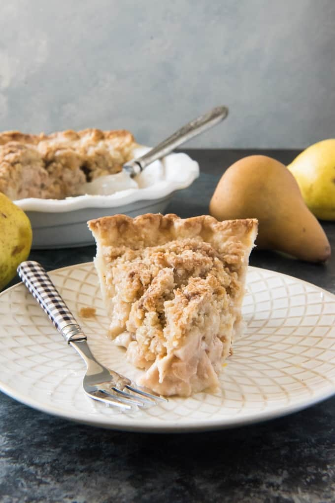 Dutch Pear & Nutmeg Pie is a warm, wonderful pie filled with Fall's other sweet, juicy and often overlooked fruit, delicately spiced with grated nutmeg and topped with a sandy, buttery streusel crumble topping.  Watch out, apple pie!  This Fall, switch up your Thanksgiving pie game with a pear pie instead of apple!  This Dutch Pear & Nutmeg Pie is a fantastic dessert that your family will go crazy over!