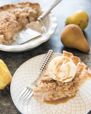 Dutch Pear & Nutmeg Pie on a plate with a fork and topped with a scoop of ice cream