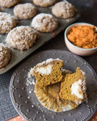 Pumpkin Streusel Muffins with Cream Cheese Filling in a muffin tin and split open on a plate in front of a bowl of pumpkin puree