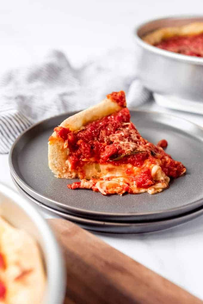 An image of a slice of homemade Chicago deep dish pizza on a plate.