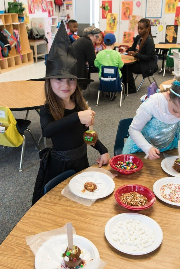 An image of a girl dressed as a witch making caramel apples.