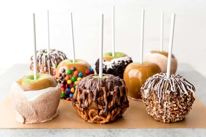An image of 8 caramel apples with different toppings.