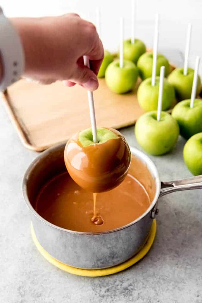An image of a hand dipping a granny smith apple into homemade caramel.