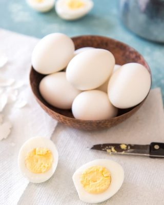 a bowl filled with whole eggs with some halved eggs around it
