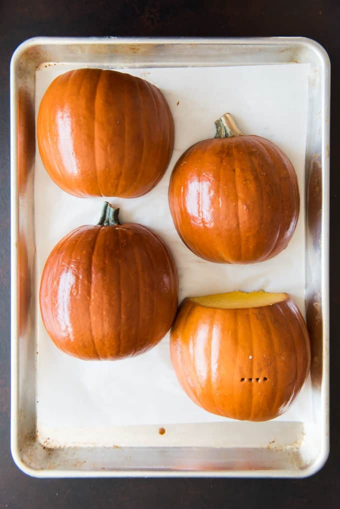 halved pumpkins on a parchment lined baking sheet