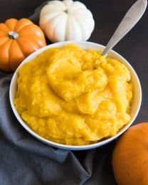 a white bowl of pumpkin puree with a spoon inside and 3 pumpkins and a blue towel around it