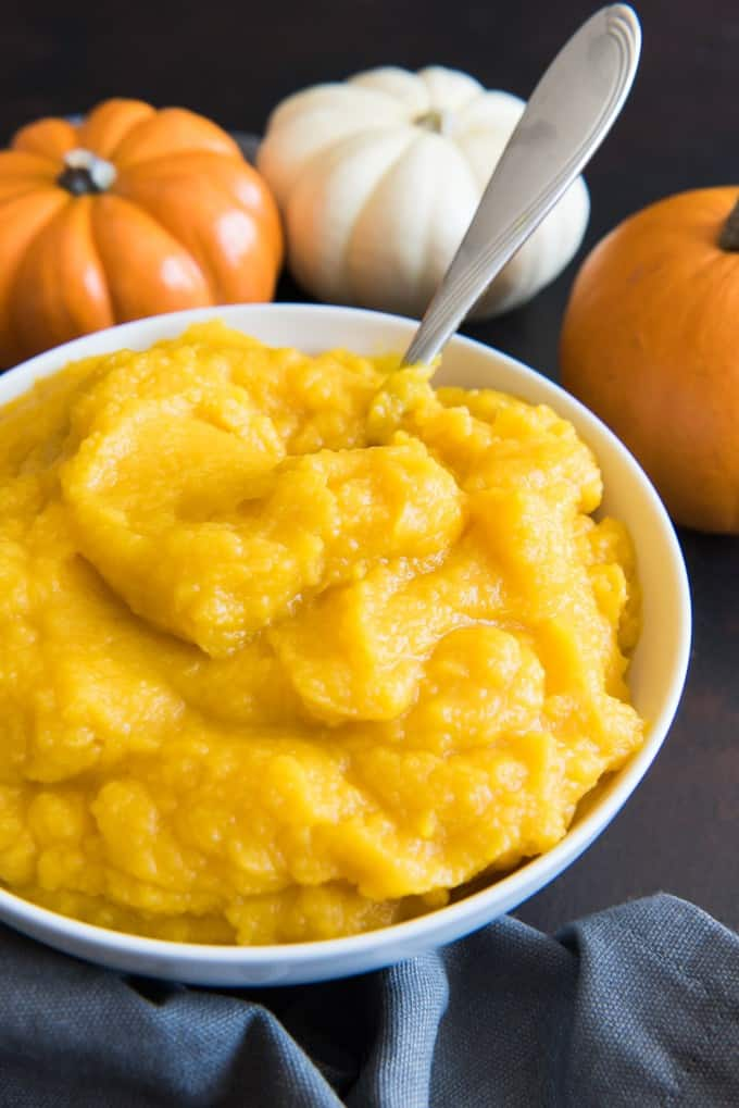 pumpkins resting behind a white bowl of pumpkin puree with a metal spoon inside