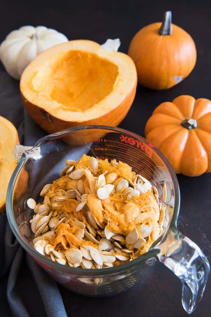 a large glass measuring cup full of pumpkin guts next to a sliced pumpkin halve and some orange and white whole pumpkins
