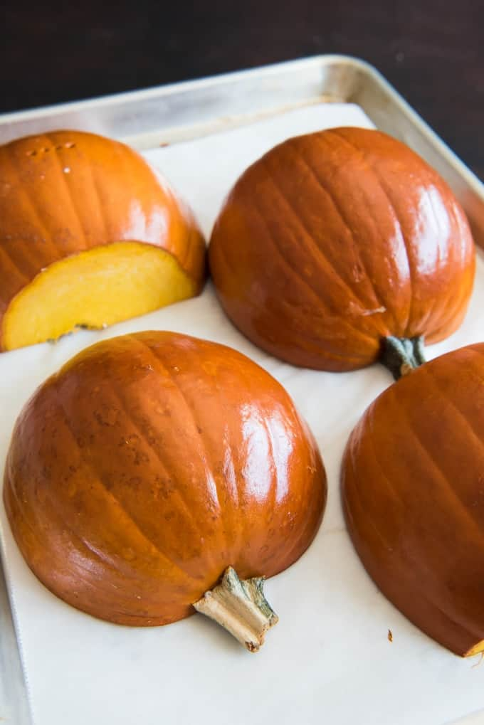 4 halves of pumpkins on a baking sheet