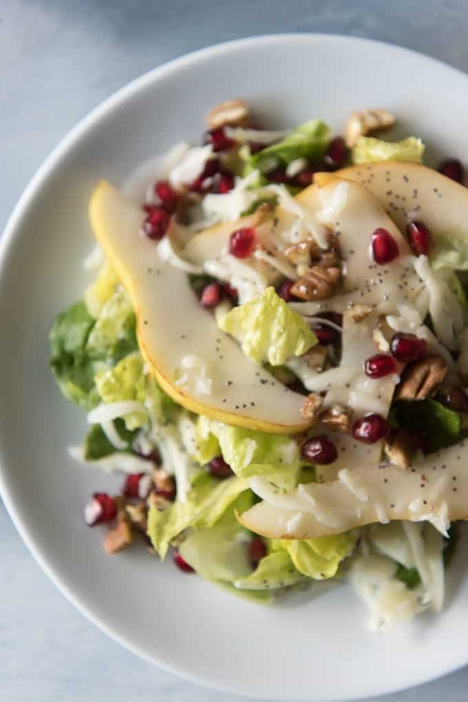 a white plate topped with winter pear salad and poppy seed dressing