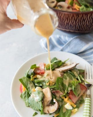 pouring honey mustard dressing onto a green salad