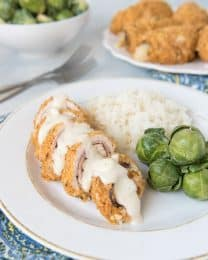 Chicken Cordon Bleu sliced and covered in sauce ona white plate next to brussel sprouts