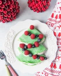 christmas tree shaped crepes on a plate with whipped cream and berries as garland