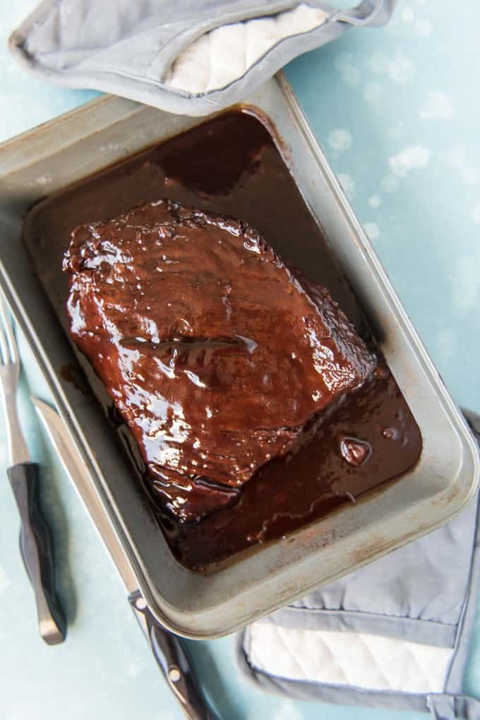 Slow Roasted Oven BBQ Beef Brisket is so tender and juicy, with a sweet & smokey hickory barbecue sauce, that no one will care that the meat wasn't cooked by a Texas pitmaster!