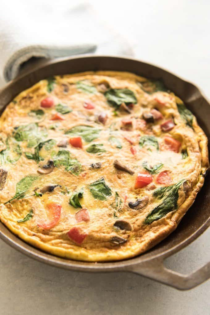 a close side view of a baked frittata in a cast iron skillet