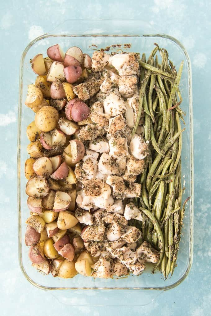 a glass 9x13 baking dish filled with rows of baked potaotes, chicken and green beans covered in seasonings