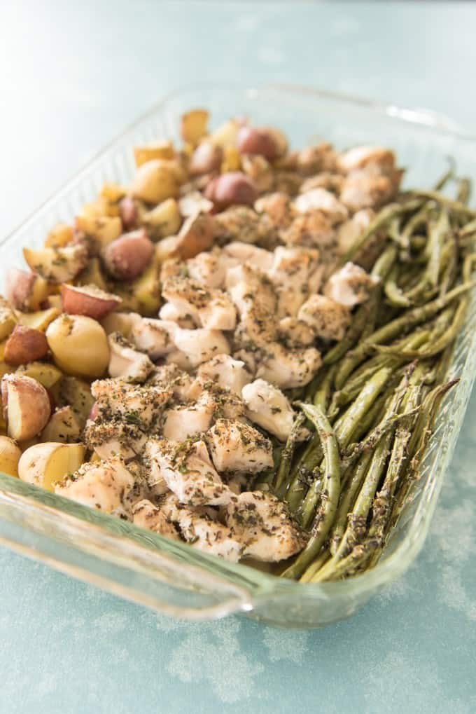 a baking dish filled with baked green beans chicken and red potatoes covered in seasonings