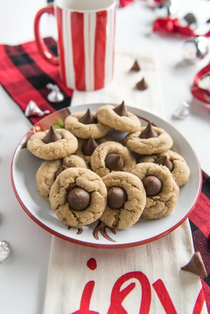 peanut butter blossom cookies on a plate in a pile while hershey kisses both wrapped and unwrapped are scattered around and a striped white and red mug rests in the background