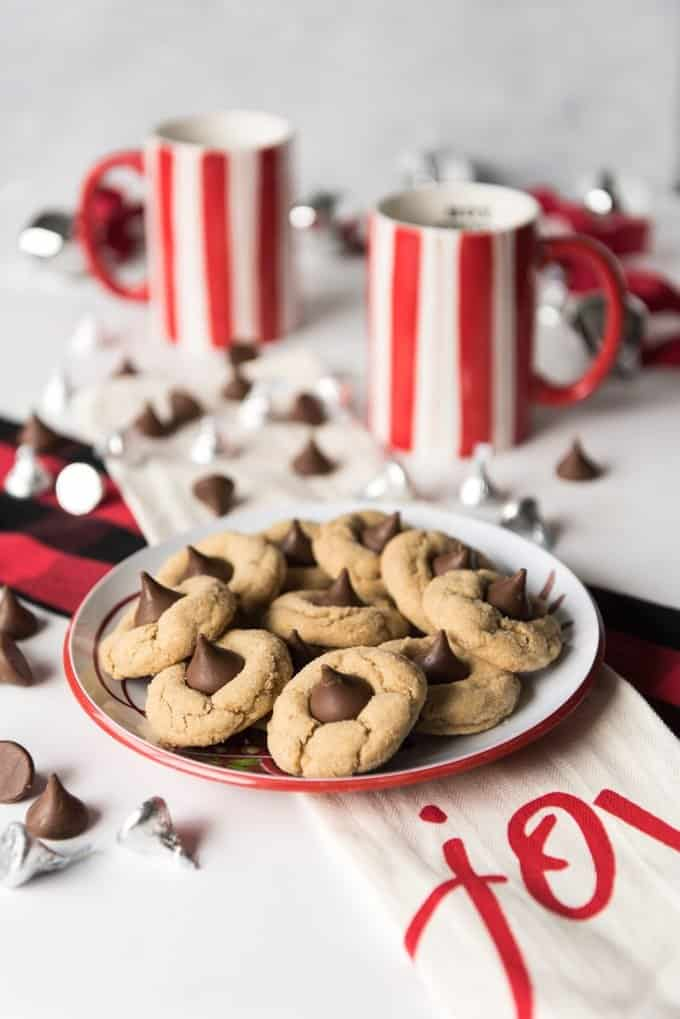 red and white striped mugs and scattered kisses around a plate of peanut butter blossom cookies