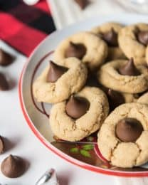 a bowl filled with peanut butteer blossom cookies with a few scattered hershey kisses around it