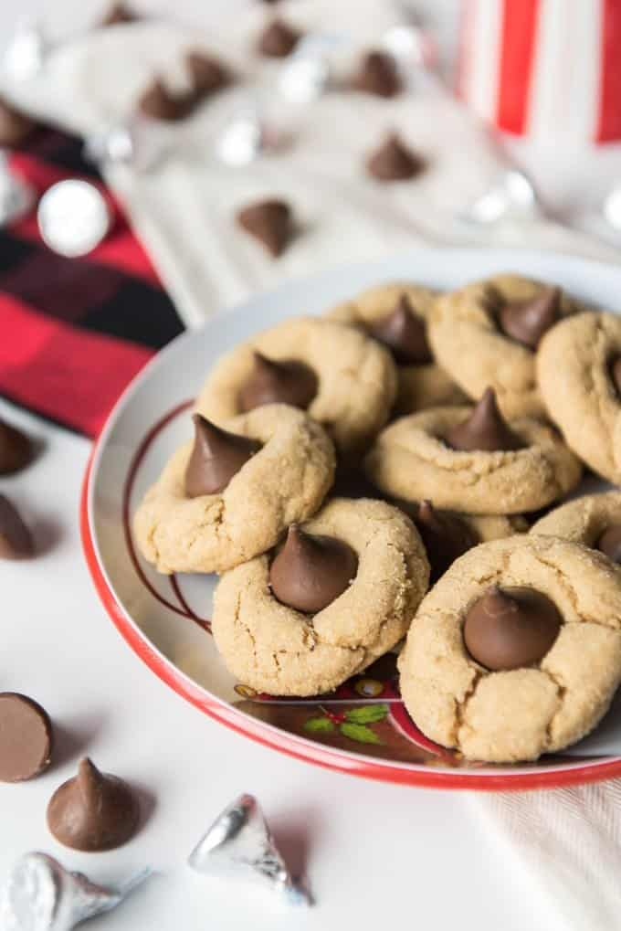 peanut butter blossom cookies on a plate with hershey kisses around them