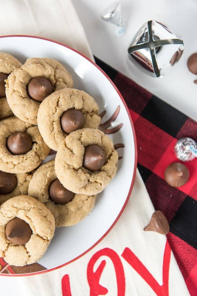 blossom cookies on a plate near a large jinglebell and more hershey kisses