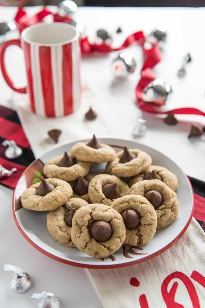 a plate full of peanut butter blossom cookies on a table with red and white decorations and mugs around it and some Hershey kisses both wrapped and unwrapped scattered on the table