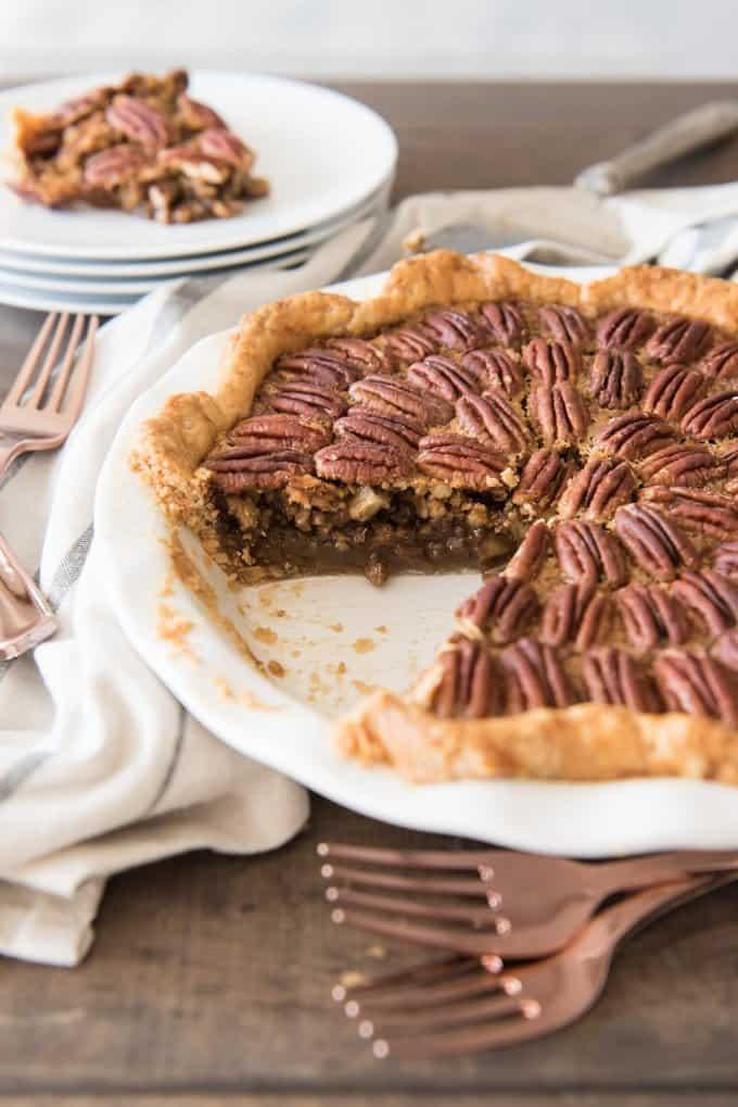 a pecan pie with a slice removed and placed on a stack of white plates with forks scattered around