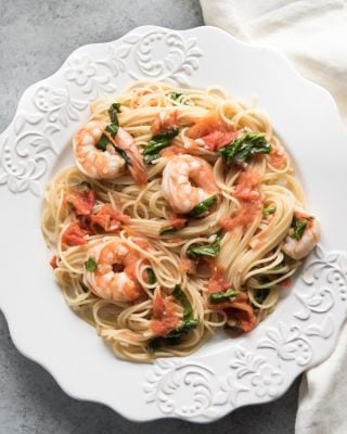 an aerial view of a white plate filled with shrimp and tomato angel hair pasta