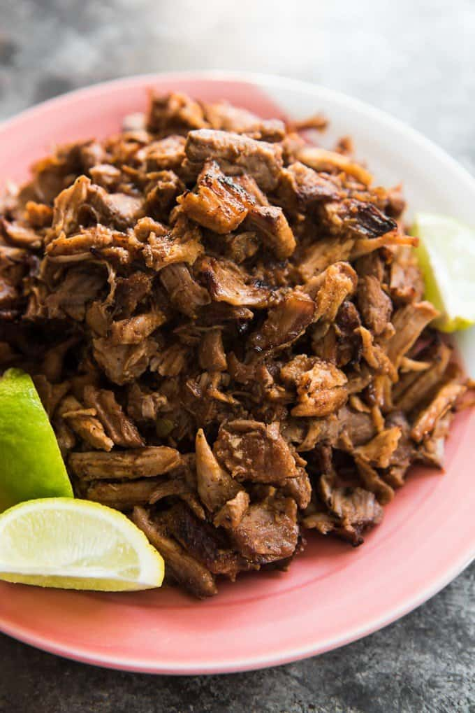 a red plate with shredded pork and lime wedges