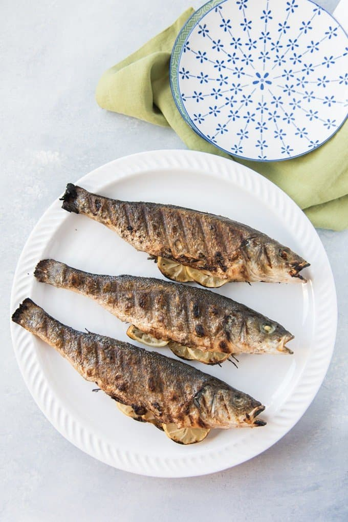 grilled fish on a white plate next to a blue and white flowered plate on a green towel