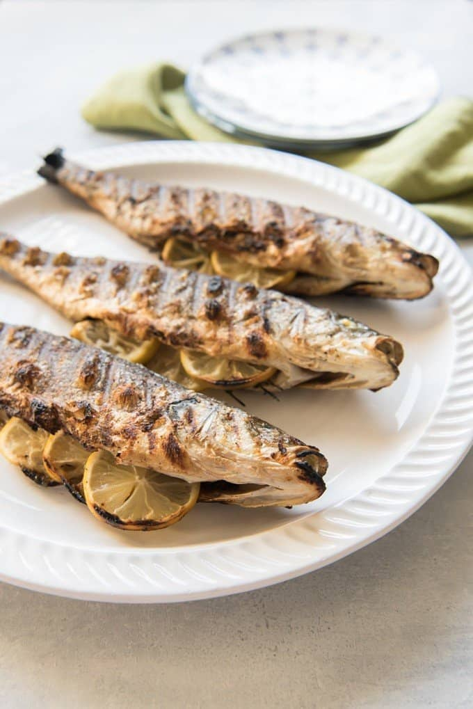 lemon stuffed and grilled whole fish on a white plate