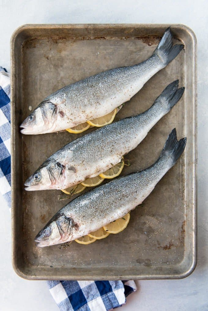 3 lemon stuffed fish on a metal baking sheet resting on a blue and white towel