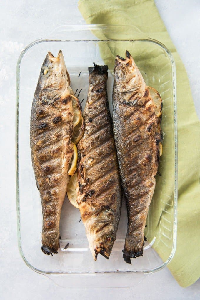 three grilled fish stuffed with lemon in a glass baking dish