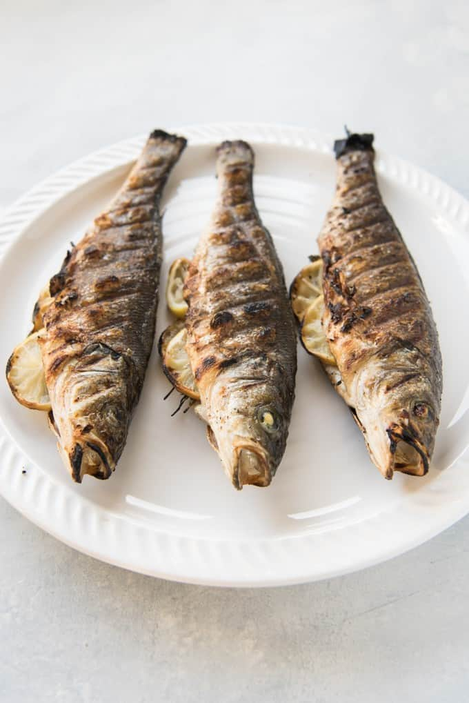 three grilled whole fish on a white platter