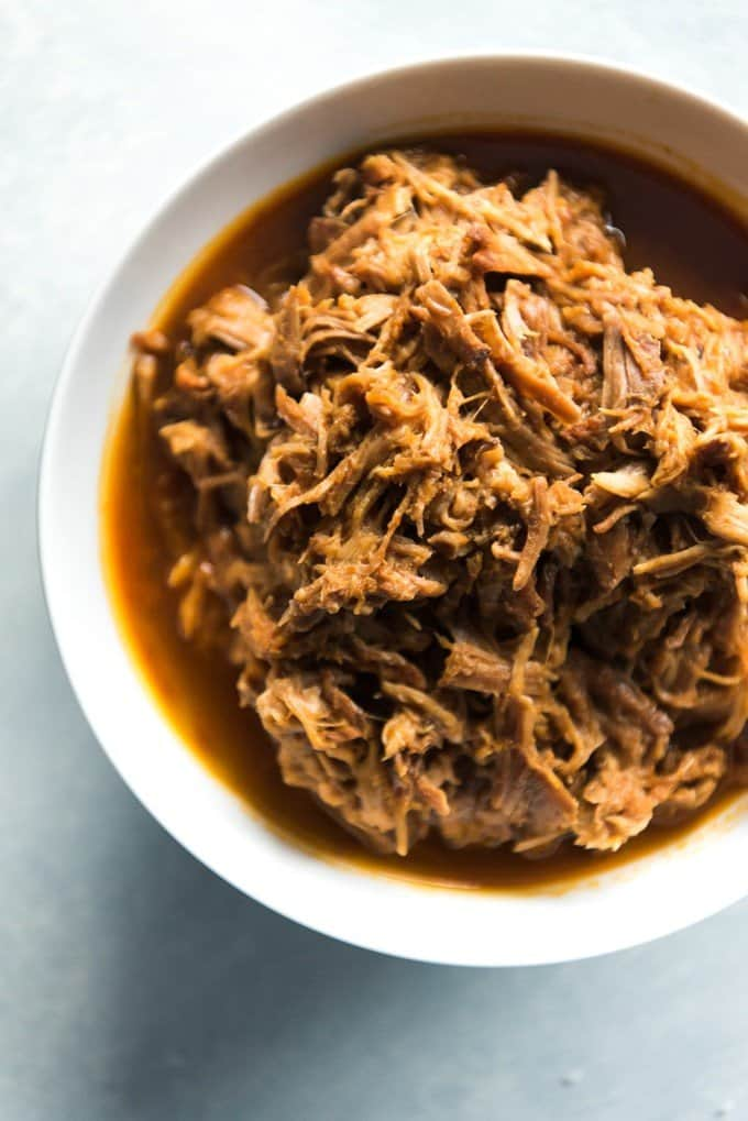 shredded pork and juices insde of a white bowl
