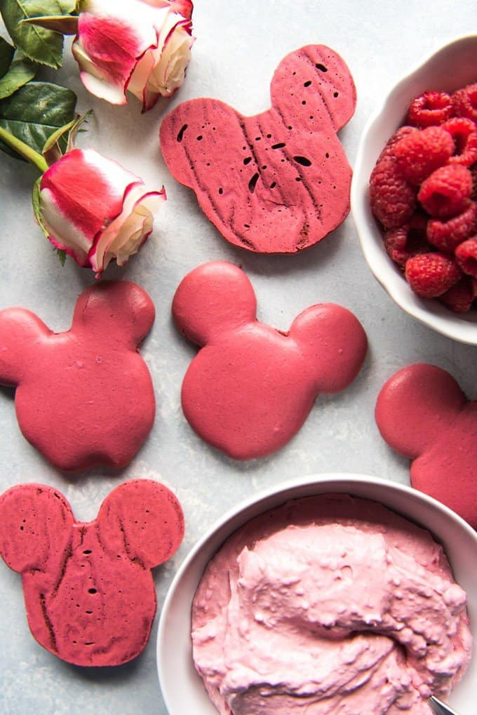 mickey mouse head shaped macaron cookies surrounded by bowls of fresh raspberries filling and fresh roses