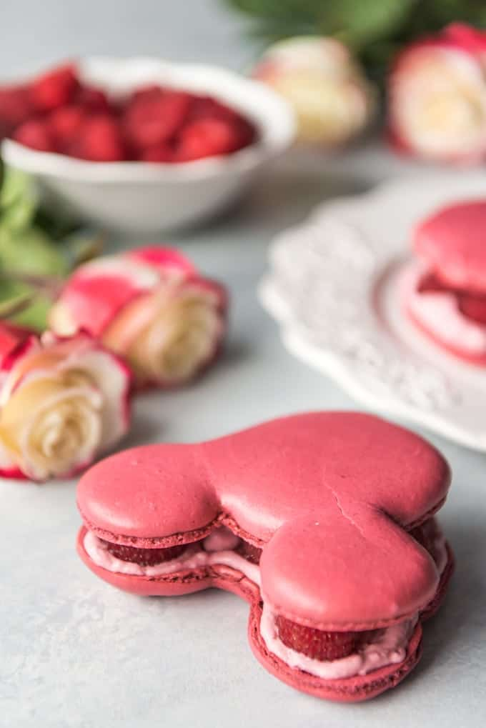 a raspberry rose macaron shaped like mickey mouse head with flowers berries and macaron in the background