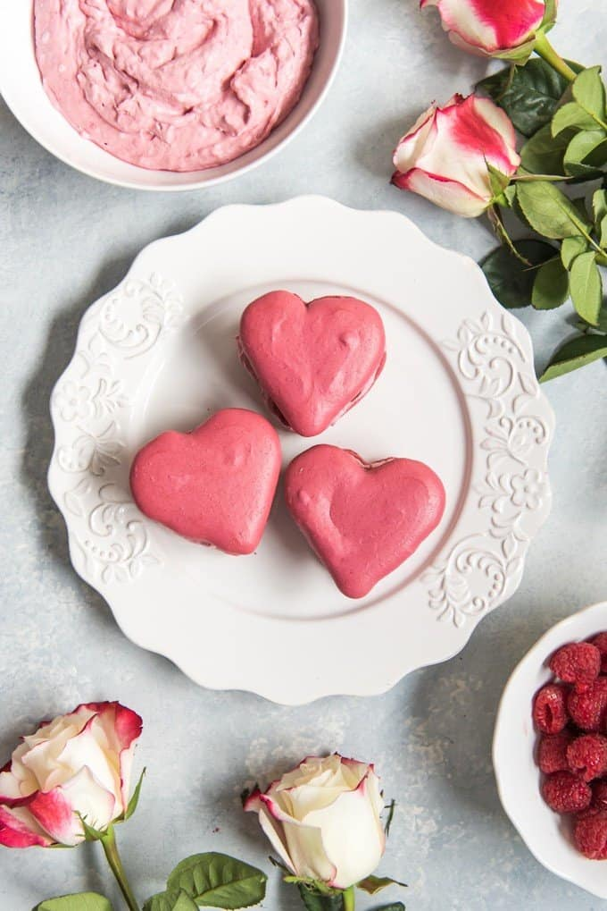 aerial view of heart shaped macarons on a plate with a bowl of filling fresh raspberries and fresh flowers around it