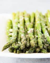 a plate with rows of asparagus topped with cheese